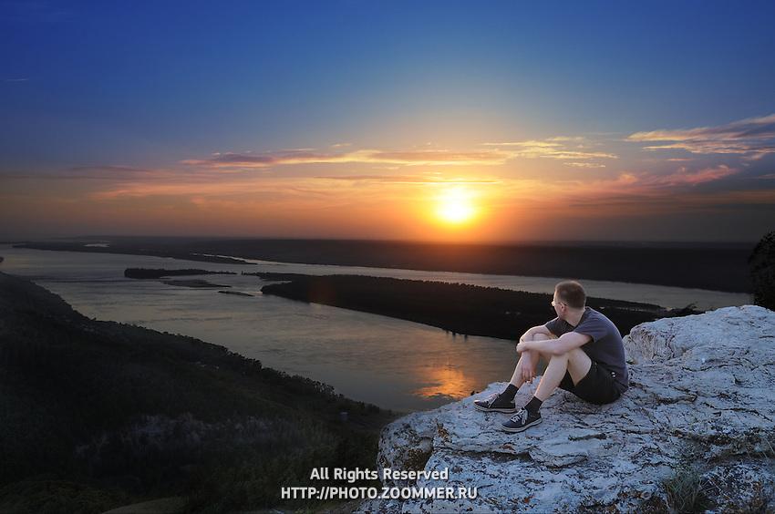 Man watching sunset in Russian National Park Samaraskaya Luka sitting on a rock