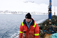 """In Faskrudsfjordur, a small fishing village on the east coast of Iceland, live goes on. The ICEAVE debate continues, but the general thoughts are to agree on not knowing enough. If Iceland should enter the EU is though more prominent in the discussion, general thoughts are against it.  .The theme song from 'Cheers' imposes it self on me while I walk the main street. The bank and the post office share a space as well as employees. I'm told that you don't really need an ID to make transfers from your account, """"it's one of the perks living in the countryside, the clerk should know you."""" The liquor store is open from five to six most days, on Fridays it is open from four. It's a fishing village, traditional one, with two trawlers a capelin processing plant and rendering..1)When the temperature gets below -10°C and the temperature of the sea is nearly 0°C every working minute seems like an hour. This Polish fisherman, who has lived in Iceland for many years, was setting out traps for a fish farming."""