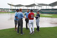GCL Red Sox manager Tom Kotchman (11) talks with umpires Mark Bass and Grant Hinson, as well as GCL Rays manager Jim Morrison (2), as the infield is under water during a game on August 3, 2015 at the JetBlue Park at Fenway South in Fort Myers, Florida.  At left is a member of the Red Sox grounds crew;  the game was suspended after two innings due to the inclement weather.  (Mike Janes/Four Seam Images)