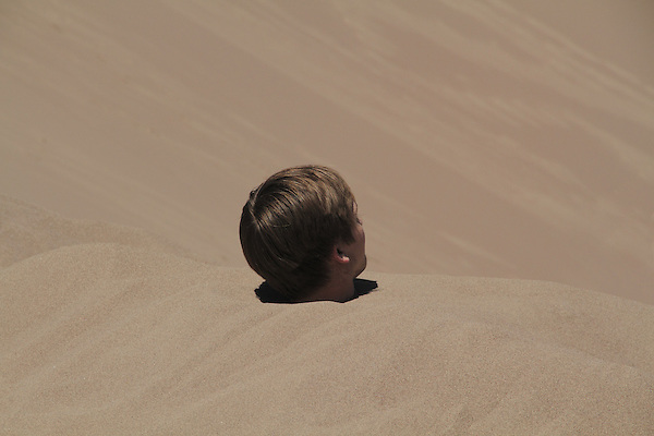 Young man buried in the Great Sand Dunes National Park, Colorado. John offers private photo trips to Great Sand Dunes National Park and all of Colorado. All year long.