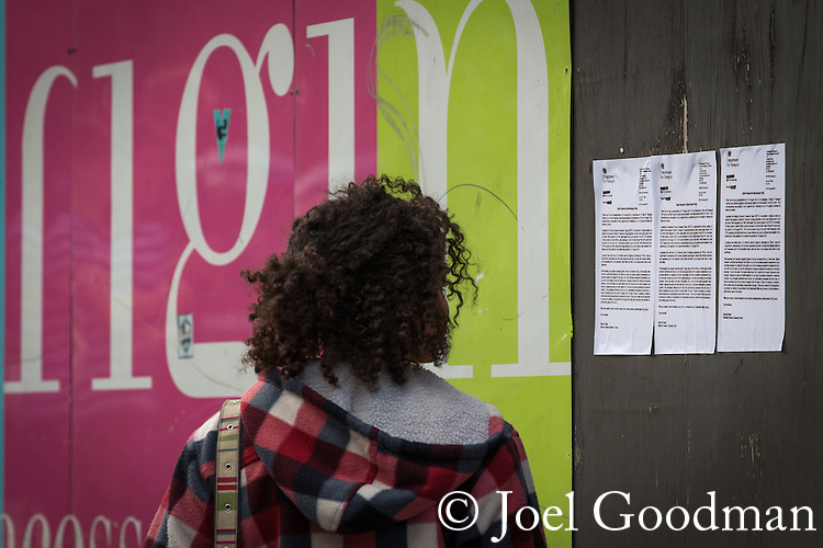 "© Joel Goodman - 07973 332324 . 22/08/2014 .  Manchester , UK . Woman looking at pasted copies of Department for Transport letter confirming right of way through village during pride , on temporary hoarding on Princess Street , just outside the perimeter of the Pride barriers . Manchester Pride "" Big Weekend "" in Manchester's "" Gay Village "" today ( 22nd August 2014 ) . Photo credit : Joel Goodman"