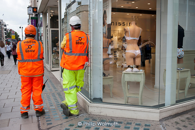Two workers in high visibility jackets outside a clothing store in Oxford Street, London.