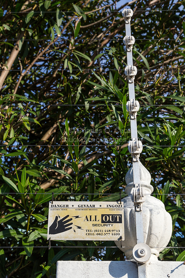 South Africa, Cape Town, Athlone Suburb.  Electric Security Wires atop Wall Surrounding Upper-class House.  Trilingual Sign in English, Afrikaans, and Xhosa.