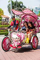 Tourists Riding in Trishaw, Melaka, Malaysia.