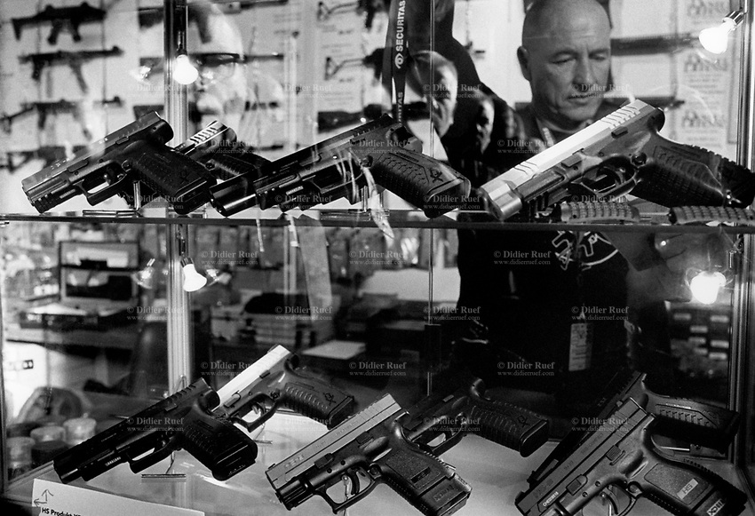 Switzerland. Canton Vaud. Lausanne. 23rd Bourse Internationale aux armes. The international gun show is a fair for hunting, sporting and melee weapons, but also for small arms, handguns and machine guns. It takes place once a year at the convention and exhibition center Beaulieu in Lausanne. A meeting point for exhibitors, customers and collectors, in order  to buy or sell modern and old weapons. Salesman and handguns. 9.12.2016 © 2016 Didier Ruef