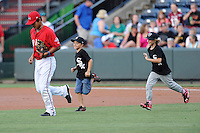 Youth ballplayers run out onto the field as Tzu-Wei Lin (36) of the Greenville Drive is announced to the crowd before a game against the Augusta GreenJackets on Friday, July 11, 2014, at Fluor Field at the West End in Greenville, South Carolina. (Tom Priddy/Four Seam Images)