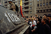 """Bucharest, Romania<br /> December 1989<br /> <br /> A captured member of Ceausescu's Securitate is taken away in an armored personal carrier surrounded by acrowd seeking revenge.<br /> <br /> The week-long series of violence that overthrew the Communist regime of Nicolae Ceausescu, ended in a trial and execution of Ceausescu and his wife Elena by firing squad. Romania was the only Eastern Bloc country to violently overthrow its Communist regime or to execute its leaders.<br /> <br /> The Romanian populace was dissatisfied with the Communist regime and leader Ceausescu's economic and development policies were blamed for the country's shortages and widespread poverty. The powerful secret police (Securitate) controlled what was essentially a police state. Ceausescu was not pro-Soviet but """"independent"""" on foreign policy. He imitated the hard-line, megalomania, and personality cults of communist leaders like North Korea's Kim Il Sung."""