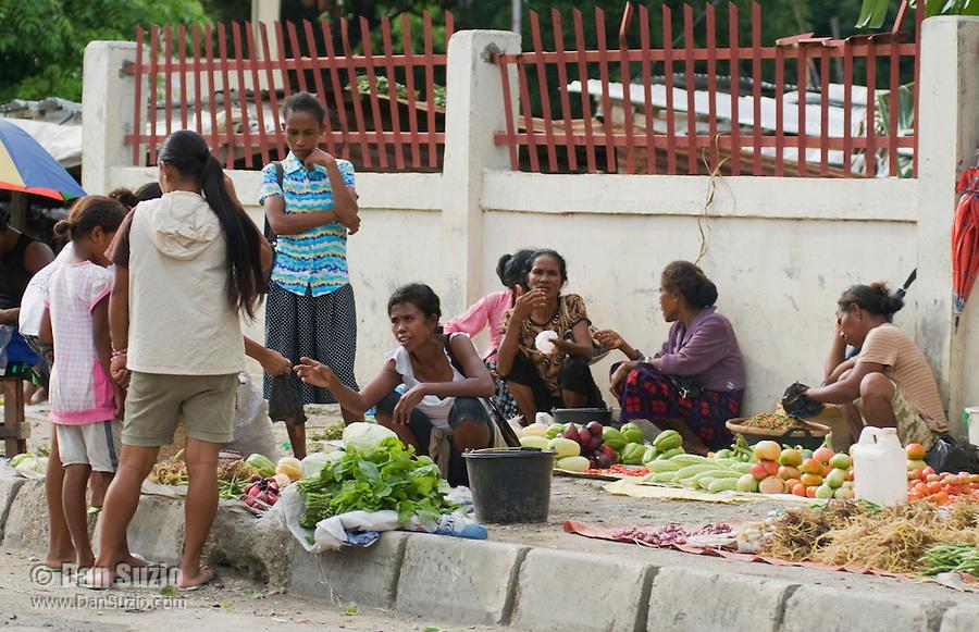 Women sell vegetables on a sidewalk in Dili, Timor-Leste (East Timor)