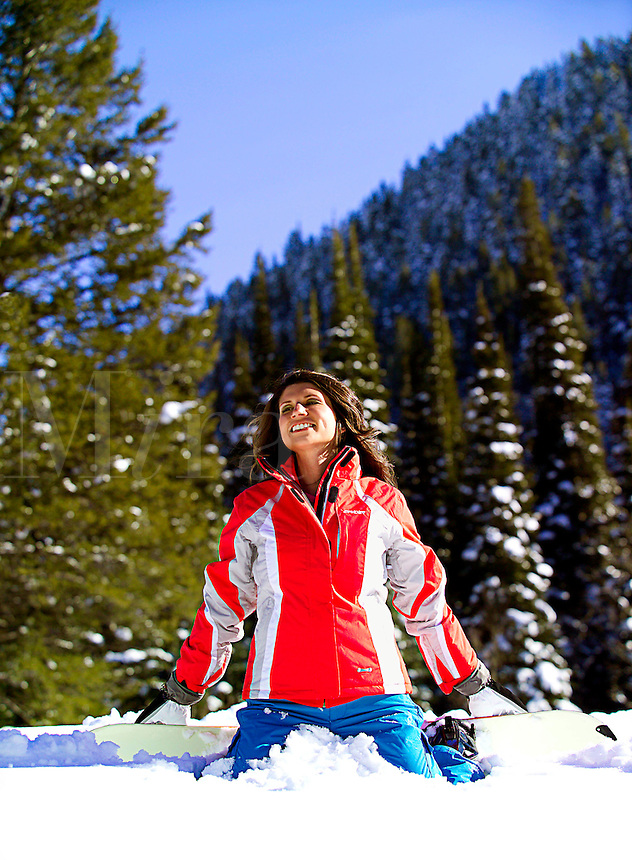 Beautiful female on snowboard sitting in snow