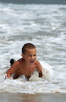 Boy playing in ocean surf in Chincoteague, Virginia.  Not model released.