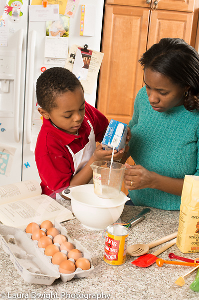 Mother and son, age 5, in kitchen, baking, measuring and pouring ingredients, measuring and pouring liquid ingredient