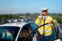 Traffic police officers in their police rapid response traffic vehicle using a mobile phone to communicate with their control room. This image may only be used to portray the subject in a positive manner..©shoutpictures.com..john@shoutpictures.com