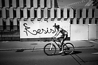 """Switzerland. Canton Ticino. Lugano. A cyclist on the road. Construction site for USi (Università della Svizzera italiana) and SUPSI (Scuola universitaria professionale della Svizzera italiana). The new campus will be opened in the autumn of 2020. On the wall, a graffiti with the word: Resist. Due to the spread of the coronavirus (also called Covid-19), the Federal Council has categorised the situation in the country as """"extraordinary"""". From March 16 the government ramped up its response to the widening pandemic, ordering the closure of bars, restaurants, sports facilities and cultural spaces. 9.05.2020 © 2020 Didier Ruef"""