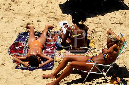 Salvador, Bahia, Brazil. Three girls relaxing on Barra beach, one reading a magazine.