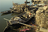 INDIA Varanasi, firewoods for cremation of dead body at Manikarnika ghat at river Ganga,  cremation is part of hindu ritual moksha hindu belief to get salvation of rebirth here / INDIEN Benares Varanasi Kashi, Anlieferung von Holz mit Booten fuer Kremation am Manikarnika Ghat am heiligen Fluss Ganges, Hindus glauben an Ritual Moksha wer hier verbrannt wird entgeht dem Kreislauf der Wiedergeburt und kommt in den Himmel