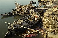 INDIA Varanasi, firewoods for cremation of dead body at Manikarnika ghat at river Ganga,  cremation is part of hindu ritual moksha hindu belief to get salvation of rebirth here / INDIEN Benares Varanasi Kashi, Anlieferung von Holz mit Booten fuer Kremation am Manikarnika Ghat am heiligen Fluss Ganges, Hindus glauben an Ritual Moksha wer hier verbrannt wird entgeht dem Kreislauf der Wiedergeburt und kommt in den Himmel