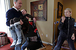 William Massart lifts his daughter Sandra Massart, 10, near his wife Olga Batiounina at the family's apartment in Durham, NC, USA, on Tuesday, Feb. 14, 2012.  Sandra Massart is being treated at Duke University Hospital in Durham, NC, for MLD, a degenerative condition.  Photo by Ted Richardson