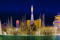 Panorama on the Paris Hotel lit-up Eiffel Tower, with the beautiful Bellagio Casino's choreographed fountains in the foreground, Las Vegas Nevada