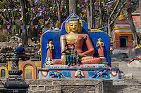 """Nepal, Kathmandu, Swayambhunath.  Two Young Boys Sitting in the Lap of a Buddha Flanking  the Stairs Leading to the Stupa at the top of the Hill.  The Buddha is Demonstrating the """"Earth is my Witness"""" Gesture.  (Bhumisparsha Mudra)."""