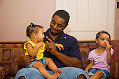 MR / Schenectady, NY. Father (22, African American) talks to and plays with his infant daughter while toddler daughter (girl, 10 months, African American & Caucasian) sits to the side, looking bored. MR: Dal4, Dal7, Dal5. ID: AL-HD. © Ellen B. Senisi