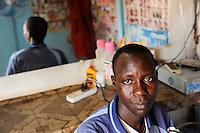 Westafrika Mali Bamako , Fluechtlingshilfe Organisation A.R.A.CE.M. betreut festsitzende Migranten , die versucht haben illegal nach Europa zu reisen, Omare Nelgida, 20 Jahre alt, aus dem Tschad, verdient Geld in einem barber shop der Organisation  - Migration Flüchtlinge / Africa Mali Bamako , refugees and migration