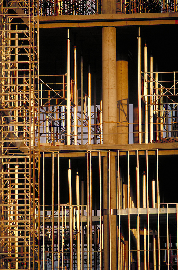 detail of temporary supports glowing in late light while multi-story building is under construction