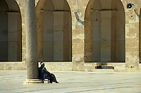 Man sitting inside the Great Mosque of Aleppo, Aleppo, Syria.