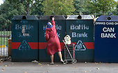 A woman uses a Haringey Council bottle bank, London.