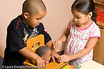 preschool 3-4 year olds family area pretend play boy and girl working together to put doll in high chair cooperation