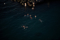 """Youths swim in the Gulf of Naples near rocks at a private """"beach"""" on Thursday, Sept. 17, 2015, in Sorrento, Italy. (Photo by James Brosher)"""
