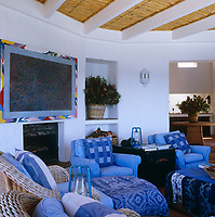 The living room is filled with comfortable armchairs and wicker chaise-longues covered in blue and white fabrics