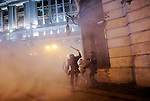 """Two riot police officers chase after a protester during clashes at the end of a demonstration organized by Spain's """"indignant"""" protesters, a popular movement against a political system that they say deprives ordinary Spaniards of a voice in the crisis, near the parliament building in Madrid during a general strike on November 14, 2012.   (c) PEDRO ARMESTRE"""