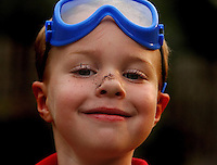 A young boy smiles as he shows off his dirty nose.