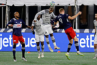 20th November 2020; Foxborough, MA, USA;  Montreal Impact forward Romell Quioto heads the ball clear from New England Revolution forward Adam Buksa during the MLS Cup Play-In game between the New England Revolution and the Montreal Impact