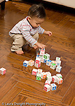 16 month old toddler boy playing with blocks making block tower Asian Chinese vertical
