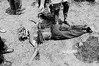 Philippines. Luzon island. San Fernando, Pampanga.70 km from Manila. Flagellation at Easter on Good Friday. A masked man lays on the ground.His arms are wide open like if he was nailed to a cross.  An empty plastic bottle has no water left. © 1999 Didier Ruef