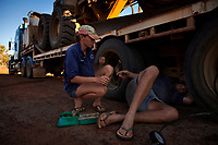 Joanna Atkins passes her husband Nick a tool as they fix a flat tyre on the Gibb River-Kalumburu Road. ''The road is keeping us small'', Nick says.