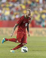 Portugal midfielder Raul Meireles (16) chip pass. In an international friendly, Brazil (yellow/blue) defeated Portugal (red), 3-1, at Gillette Stadium on September 10, 2013.