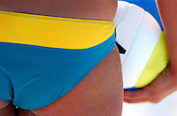 A female beach volleyball player waits to serve