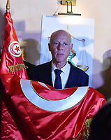 Conservative academic Kais Saied kisses the Tunisian flag as he celebrates his victory in the Tunisian presidential election in the capital Tunis on October 13, 2019. - Saied won a landslide victory in Tunisia's presidential runoff, sweeping aside his rival, media magnate Nabil Karoui, state television Wataniya said. It said he scooped almost 77 percent of the vote, compared to 23 percent for Karoui.