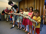 Gabe Kerschner, with Wild Things, left, and a group of kids hold Miss Piggy during a presentation at the Carson City Library, in Carson City, Nev., on Wednesday, July 30, 2014.<br /> Photo by Cathleen Allison