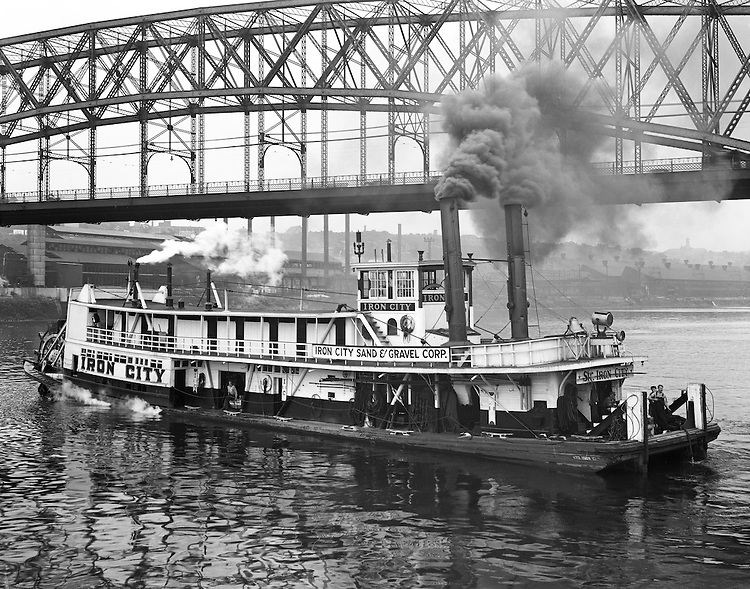 The Sir Iron City Towboat operating on the Monongahela River next to the Smithfield Street Bridge. The boat was a Sternwheel Towboat built around 1903 and designed to move coal barges.