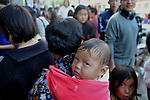 A child being wrap around by a cloth on his mother's back, Thimpu market. A typical Bhutanese way of carrying children on the back. . Arindam Mukherjee..