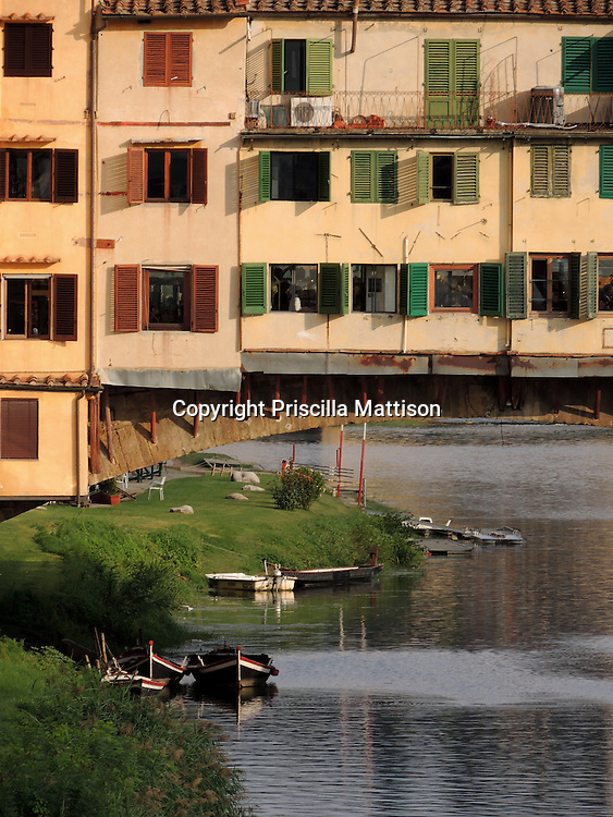 Florence, Italy - October 3, 2012:  Afternoon light falls on the shops built along the Ponte Vecchio.