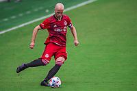 ORLANDO, FL - APRIL 24: Michael Bradley #4 of Toronto FC kicks the ball during a game between Vancouver Whitecaps and Toronto FC at Exploria Stadium on April 24, 2021 in Orlando, Florida.