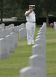 5/29/05--Jim Mehrmann, Capt. U.S. Navy Ret. salutes at the grave site of a soldier at the Houston VA National Cemetery on the day before Memorial Day.  Mehmann says that he comes to the cemetery each year and visits as many graves as possible.  He salutes at graves with American flags but stops to pay his respects at each grave. It is his goal to eventually stop at each grave in the cemetery.    Photo by Steve Campbell/Houston Chronicle     HOUCHRON CAPTION (05/30/2005) SECNEWS COLORFRONT:  HIS ANNUAL DUTY:  Jim Mehrmann, a retired U.S. Navy captain, says he comes to the Houston National Cemetery every year to visit as many graves as he can.