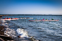 Three six-person outrigger canoes launching into Seaplane Lagoon at Encinal Park on San Francisco Bay's eastern shores.