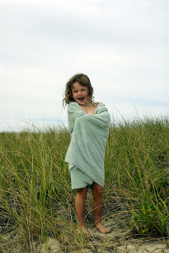 Girl wrapped in a beach towel walking through dune grass, Brewster, Cape Cod, MA<br />