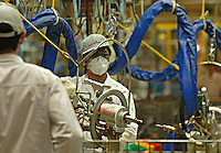 A worker with a high-tech welding gun at the new Guangzhou Honda Automobile Co. Ltd. factory. The plant built at a cost of 140 million US$ is one of the most advanced car plants in the world. It has a state of the art production line as well as the world's first total water re-cycling sytem..