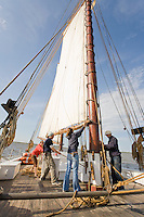 Deck Hands, hoisting the main sail, on the Historic Tall Ship, A.J. Meerwald, Delaware Bay, Cumberland County, New Jersey